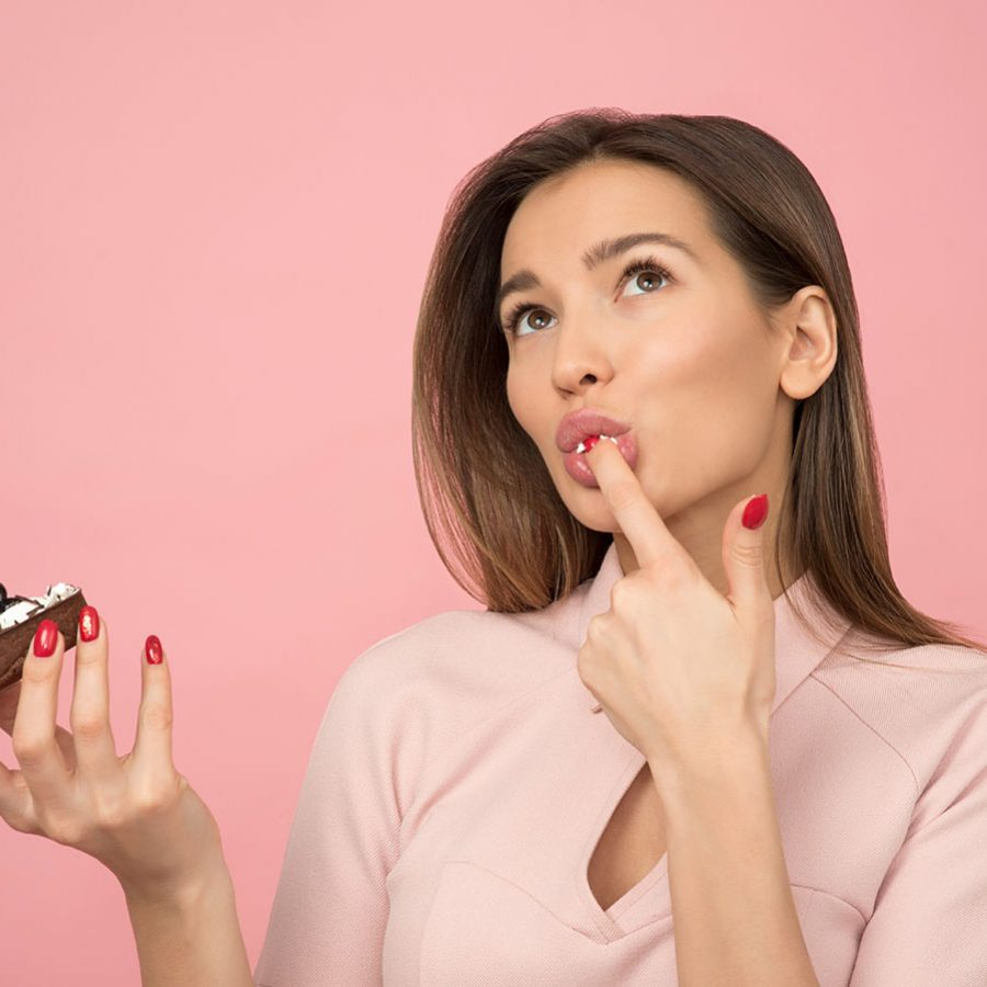 woman-eating-cupcake-while-standing-near-pink-background-1036621